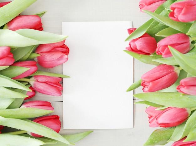 空白の白いグリーティングカードとチューリップの美しい花束 無料写真