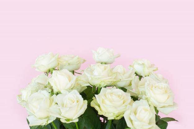 Красивый букет белых роз на розовом фоне Premium Фотографии