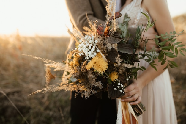Beautiful bouquet of wild flowers in the hands of the bride Free Photo