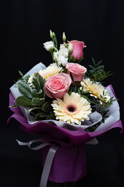 Beautiful bouquet with pink roses and gerberas on a black wall. Premium Photo