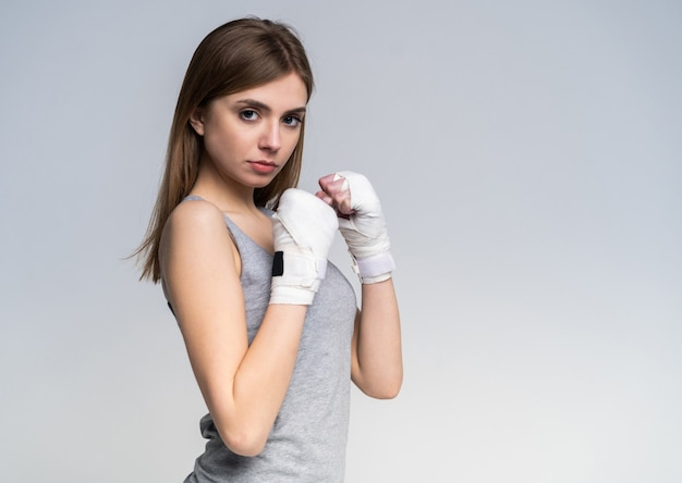 Beautiful boxer girl wearing sportive clothing and gloves practicing in the studio over gray. Premium Photo