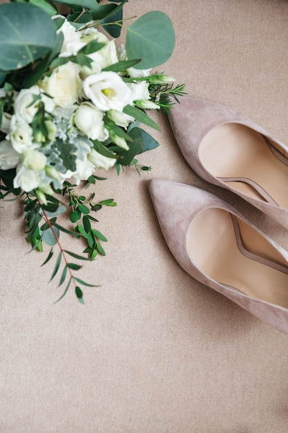Beautiful bridal shoes are standing next to a bouquet of flowers Free Photo