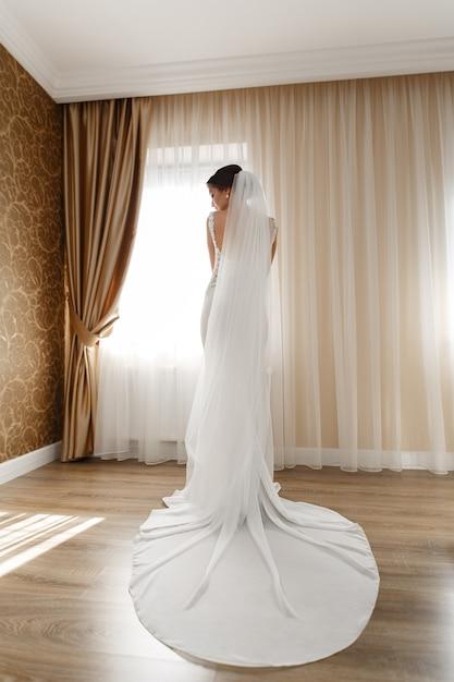 Beautiful bride in chic long dress indoor in hotel room Premium Photo