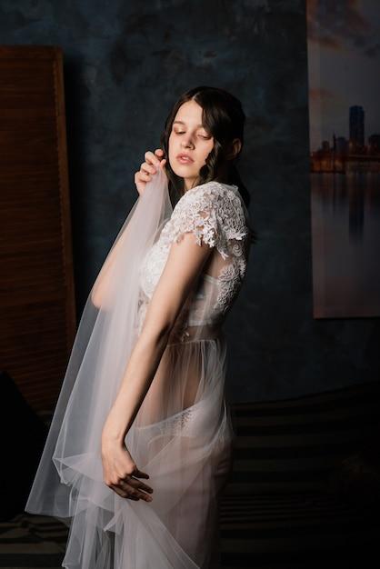 그녀의 침실과 스튜디오에 앉아 흰색 란제리에 아름 다운 신부. 웨딩 컨셉의 아침 프리미엄 사진
