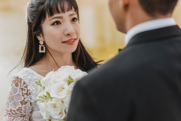 Bella sposa che esamina gli occhi dello sposo mentre tiene il mazzo Foto Gratuite