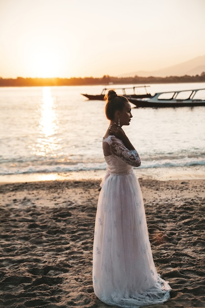 Beautiful bride posing on the beach behind sea at sunset Free Photo