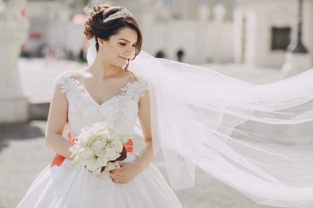 Beautiful bride in a white dress and a crown on his head in a park and holding bouquet Free Photo