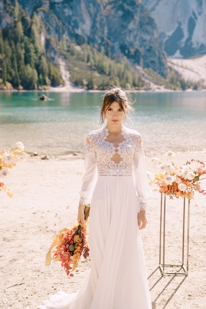 Beautiful bride in a white dress with sleeves and lace, with a yellow autumn bouquet, posing at lago di braies in italy Premium Photo