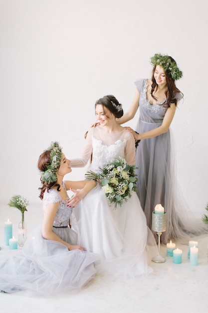 Premium Photo Beautiful Bride In A White Wedding Dress Holding Bouquet And Sitting On The Vintage Chair With Bridesmaids In Blue Grey Dresses And Wreathes