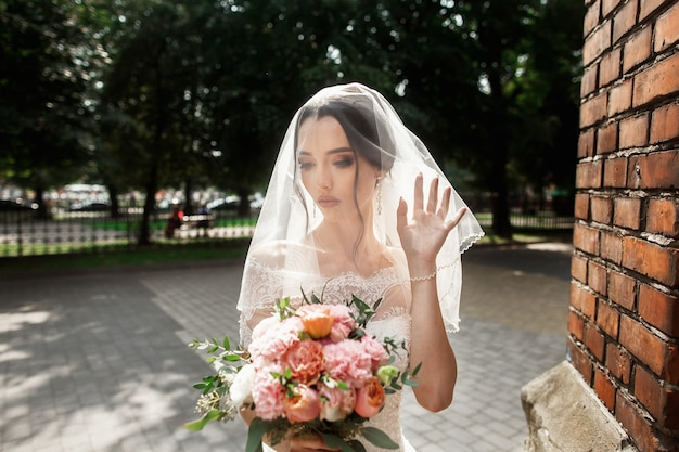 Beautiful bride with bridal veil on face posing near the red wall of old gothic church Premium Photo