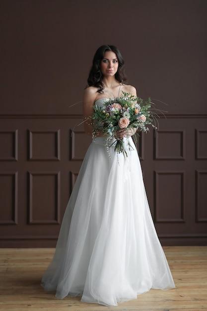 花の花束とエレガントなウェディングドレスの美しい花嫁の女性 無料写真