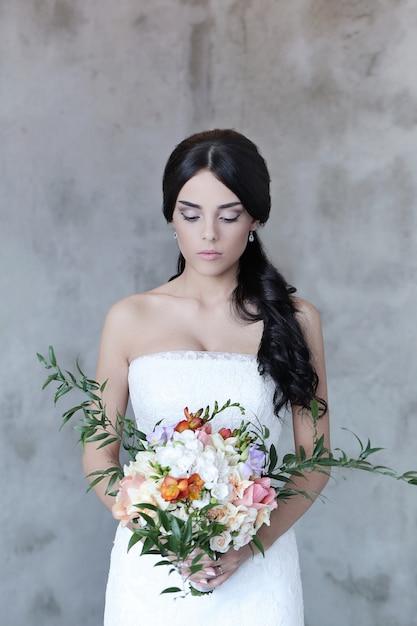 Красивая невеста женщина в свадебном платье держит букет цветов Бесплатные Фотографии