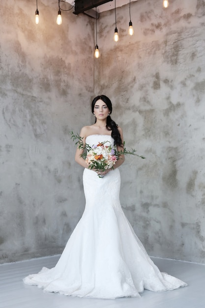 Beautiful bride woman in wedding dress holding a bouquet of flowers Free Photo