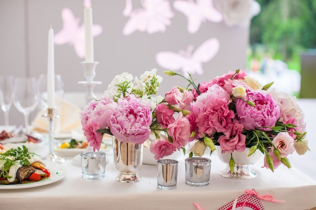 Beautiful bright bouquet of peony on the wedding table in vase Premium Photo