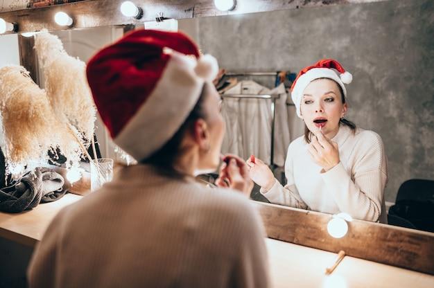 白いセーターの美しい茶色の髪の女性は化粧鏡で見えます Premium写真