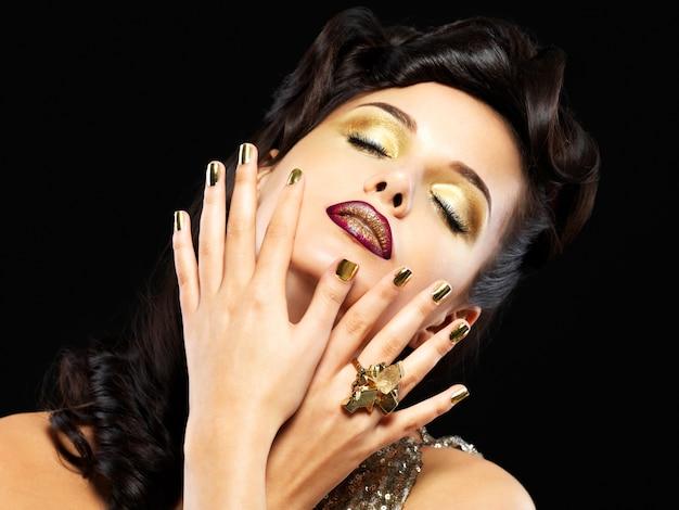 金色の爪と目のスタイルのメイクアップを持つ美しい黒髪の女性-黒い背景に 無料写真