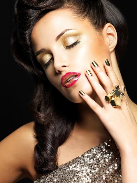 Bella donna brunet con unghie d'oro e trucco stile degli occhi - su sfondo nero Foto Gratuite