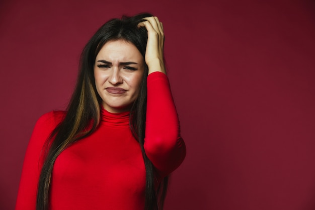 Beautiful brunette baffled caucasian girl dressed in red pullover is scraping her hair Free Photo