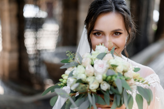 Beautiful brunette bride is looking straight and holding wedding bouquet near face Free Photo