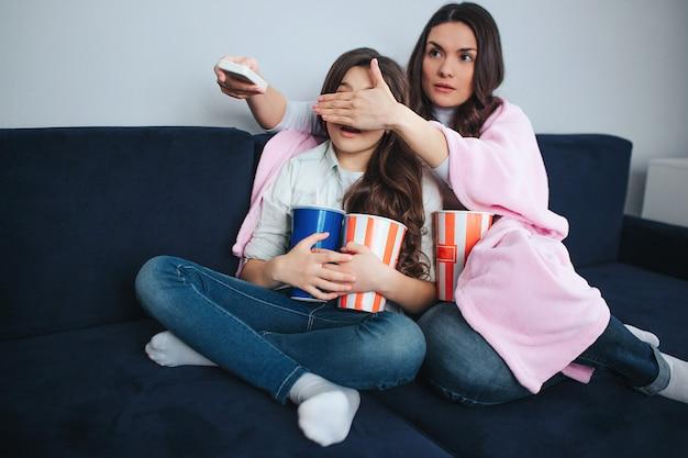 美しいブルネットの白人の母と娘は部屋に一緒に座っています。ママは少女の目を覆った。彼女はリモートコントロールを保持し、嫌悪感を楽しみにしています。娘はバセットポップコーンとコーラを保持します。 Premium写真