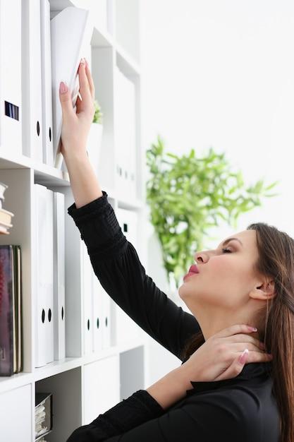 Красивая брюнетка женщина-клерк ищет нужный документ Premium Фотографии