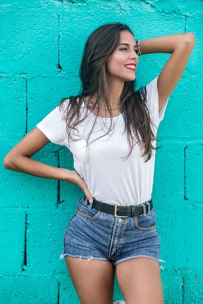 Beautiful brunette female standing by turquoise wall Premium Photo