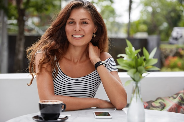 Beautiful brunette female with glad expression in outdoor terrace cafe Free Photo