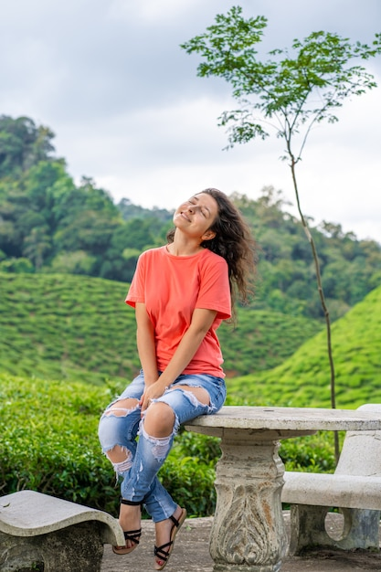 Beautiful brunette girl posing in the middle of the tea valley between green tea bushes. Premium Photo