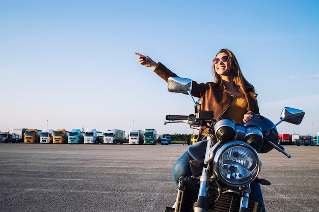 Beautiful brunette girl sitting on retro style motorcycle and pointing finger up Free Photo