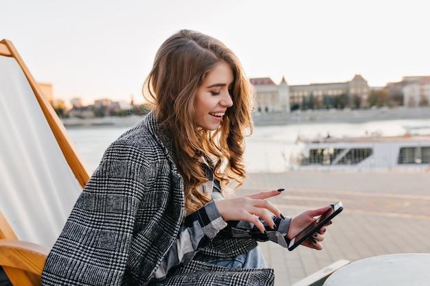 Красивая брюнетка девушка текстовое сообщение, отдыхая на шезлонге на фоне города в холодный день Бесплатные Фотографии