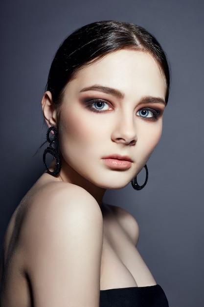 Beautiful brunette girl with big blue eyes jewelry Premium Photo