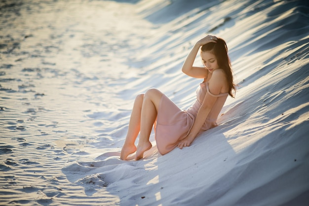 Beautiful brunette lady rests on white sand in the rays of sun Free Photo