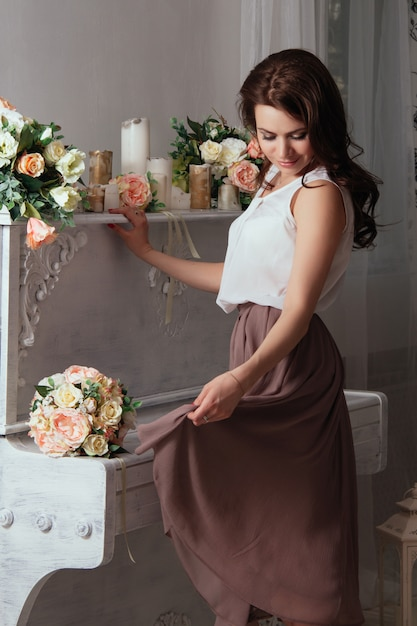 Beautiful brunette near the old piano on which lay bouquets of roses Premium Photo