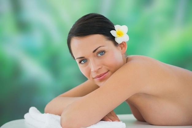 Beautiful brunette relaxing on massage table smiling at camera Premium Photo