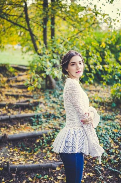 Красивая брюнетка с косами вокруг головы в стильной винтажной белой кружевной блузке с длинным рукавом в осеннем парке Premium Фотографии