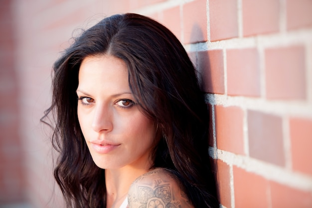 Beautiful brunette with red brick wall of background Premium Photo