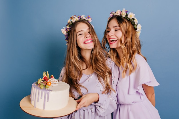 Красивая брюнетка женщина в фиолетовом платье держит торт ко дню рождения Бесплатные Фотографии