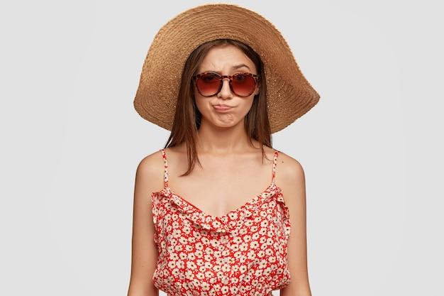 Красивая брюнетка в летней шляпе, платье, недовольно поджимает губы, чувствует неудовольствие Бесплатные Фотографии