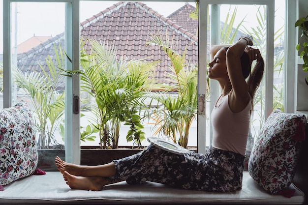 Beautiful brunette woman in loft home in tropical location. Premium Photo