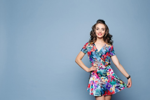 Beautiful brunette woman in stylish floral dress holding its skirt with arm. Premium Photo