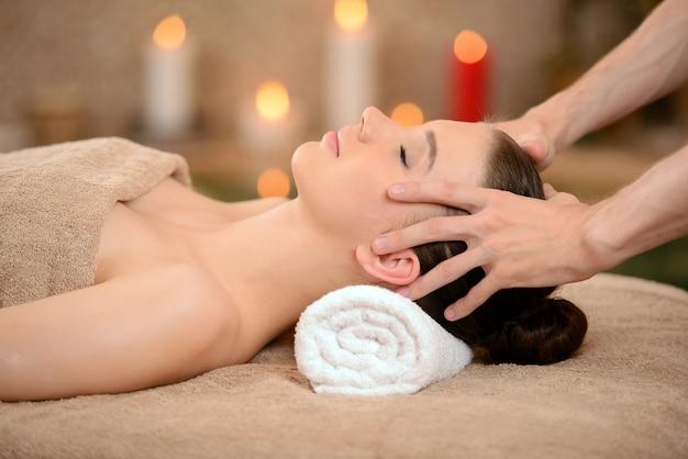 Beautiful brunette woman taking head massage. Premium Photo