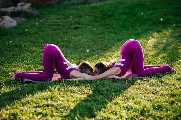 Красивая брюнетка женщина, носящая тесную активную одежду, выполняя позы йоги в парке на фиолетовых циновках с мягкими вспышками солнца, проникающими сквозь деревья Premium Фотографии