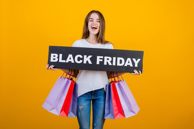 Beautiful brunette woman with colorful shopping bags and copyspace text black friday sign banner isolated over yellow Premium Photo