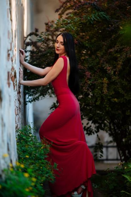 カーリーボブの短い髪、繊細な化粧、公園で赤いショートドレスの赤い唇の美しいブルネットの女性。夏のイベントでのファッションの官能的なポーズ。戸外で Premium写真