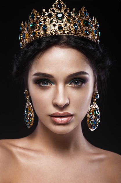 Beautiful brunette woman with a golden crown, earrings and professional evening make-up Premium Photo