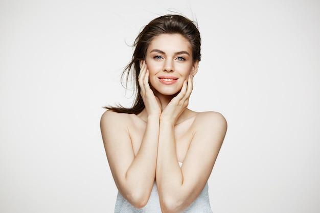 Красивая брюнетка женщина с здоровой свежей кожей и летающими волосами, улыбаясь трогательно лицо. Бесплатные Фотографии