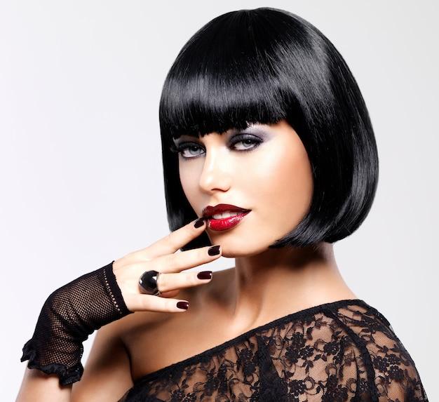 총된 검은 헤어 스타일으로 아름 다운 갈색 머리 여자입니다. 밝은 빨간색 섹시한 입술로 여성 모델의 근접 촬영 초상화 무료 사진