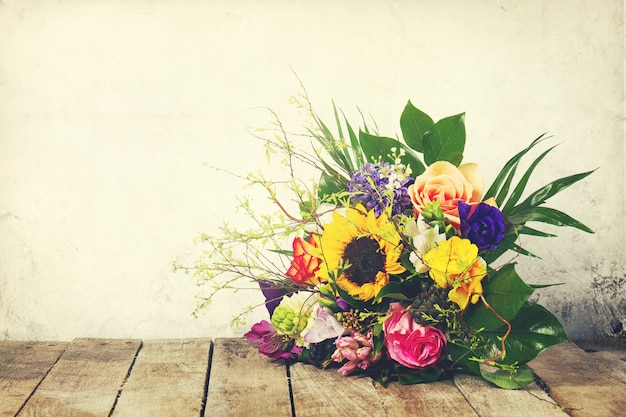 Beautiful bunch of flowers on wooden background. Horizontal. Vintage toning. Free Photo