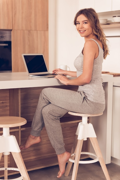 Beautiful business woman in home clothes is using a laptop. Premium Photo