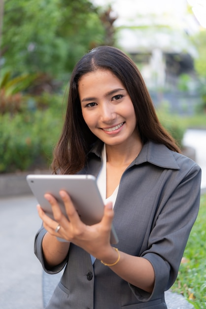 Beautiful business woman using ipad for outdoor working Premium Photo